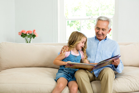 picture book: Smiling girl and granddad with picture book while sitting on sofa