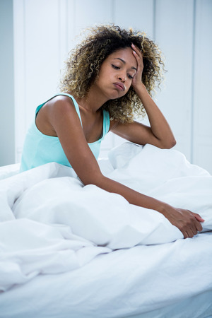 tensed: Tensed woman sitting on bed with hand on forehead in bedroom