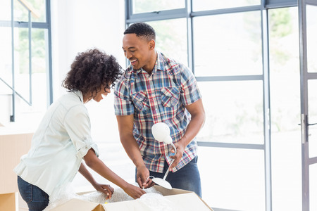 black couple: Young couple unpacking carton boxes in their new house