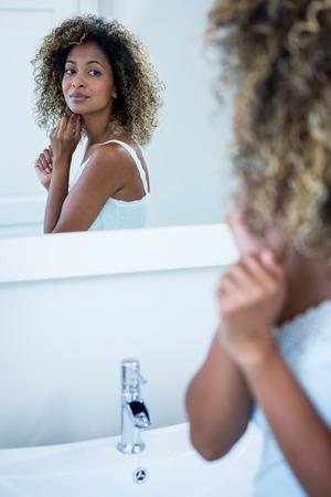 woman mirror: Reflection of woman looking in bathroom mirror