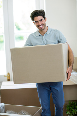 man carrying box: Portrait of young man carrying box in his new house