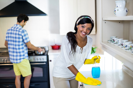 Woman cleaning the kitchen and man cooking food in background at home