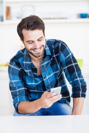 text messaging: Man text messaging on mobile phone in the kitchen Stock Photo