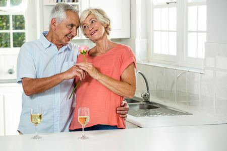 tomando refresco: Sonriente pareja senior con rosa mientras está de pie en la cocina Foto de archivo