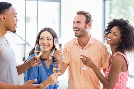 toasting wine: Friends toasting wine glasses at home Stock Photo