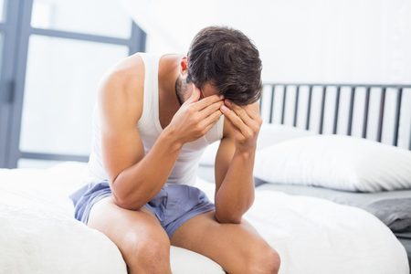 tensed: Tensed young man sitting on bed in bedroom