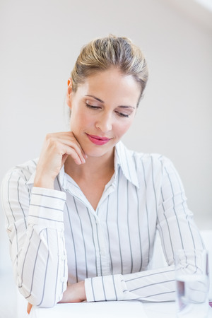 Happy businesswoman sitting with hand on chin in office Stock Photo