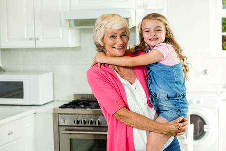 carrying girl: Portrait of smiling granny carrying girl while standing in kitchen Stock Photo