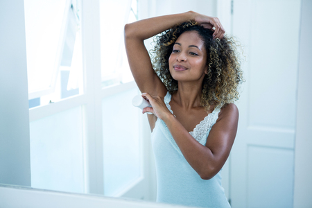 underarms: Young woman applying powder on her underarms in bathroom Stock Photo