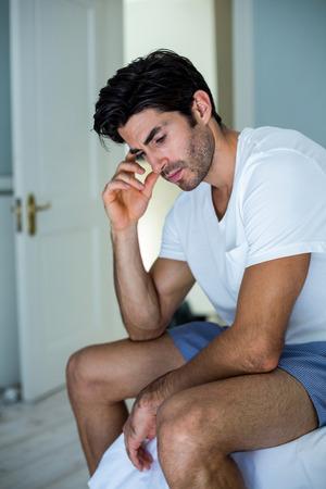 tensed: Tensed man sitting on bed in bedroom at home