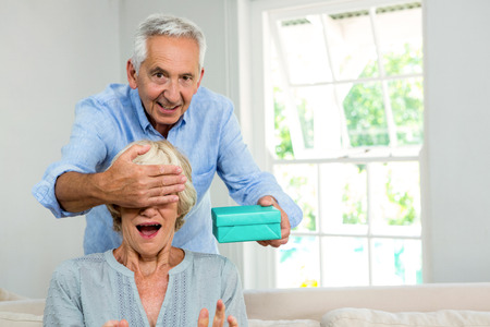 Portrait of senior man covering woman eyes to give surprise at home