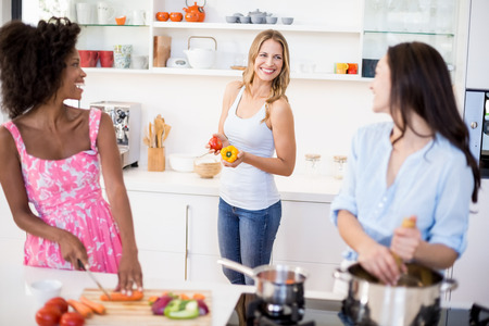 curly hair woman: Friends interacting while preparing a meal in kitchen at home