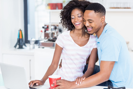 worktop: Happy couple using laptop on kitchen worktop