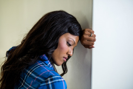 tensed: Tensed woman leaning on wall at home Stock Photo