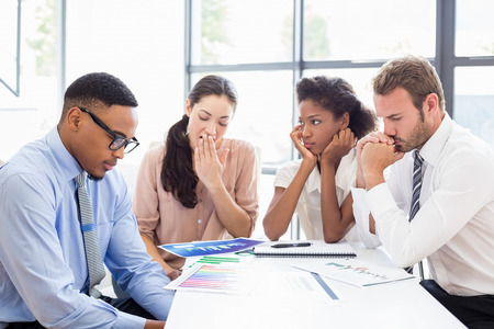 tensed: Tensed businesspeople sitting at table during a meeting in office