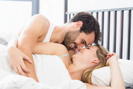 each other: Young couple embracing each other on bed in the bedroom