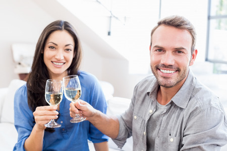 toasting wine: Portrait of young couple toasting wine glasses at home