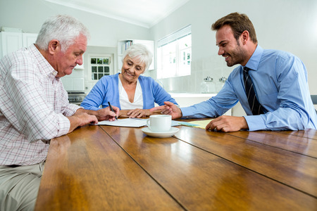 Senior couple discussing with agent while sitting at table in home