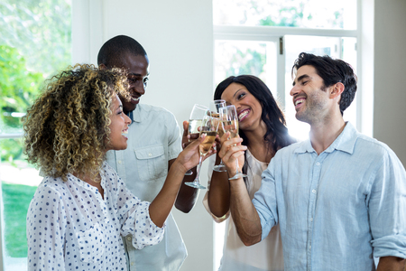 toasting wine: Happy friends toasting wine glasses at home Stock Photo