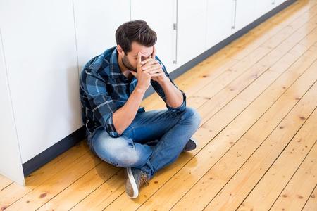 tensed: Tensed man sitting on wooden floor at home