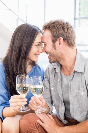 toasting wine: Young couple toasting wine glasses at home Stock Photo