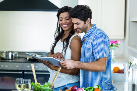 recipe book: Young couple looking at recipe book in kitchen at home Stock Photo