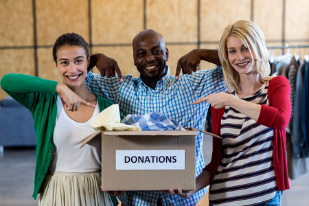 selfless: Portrait of colleagues holding and pointing at donation box