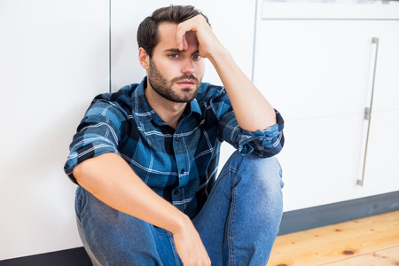 tensed: Tensed man with hand on forehead sitting on wooden floor at home