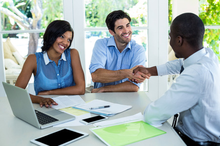 Happy couple shaking hands with real estate agent at home