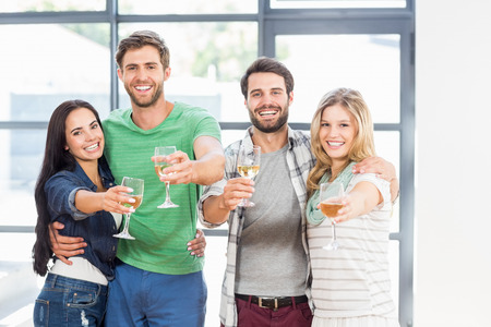standing together: Two cute couple smiling with alcohol glass in hand at home