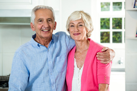 arm around: Portrait of retired couple with arm around while standing at home