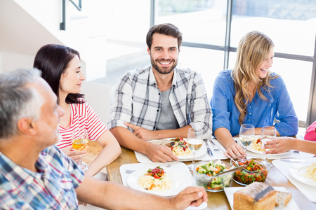 dinning table: Portrait of man sitting with friends at dinning table while having meal Stock Photo
