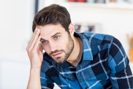 tensed: Close-up of tensed young man at home Stock Photo