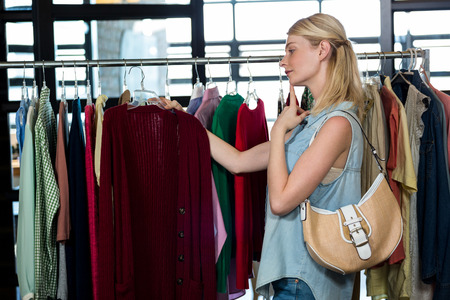 Woman selecting an apparel while shopping for clothes in apparel shop