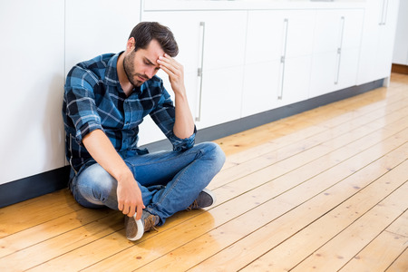 hand on forehead: Tensed man with hand on forehead sitting on wooden floor at home