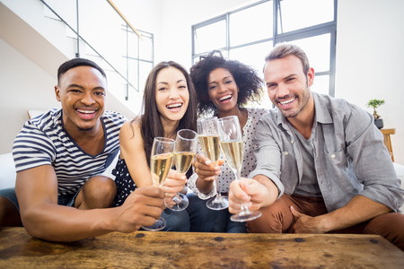Portrait of friends toasting glasses of champagne in living room