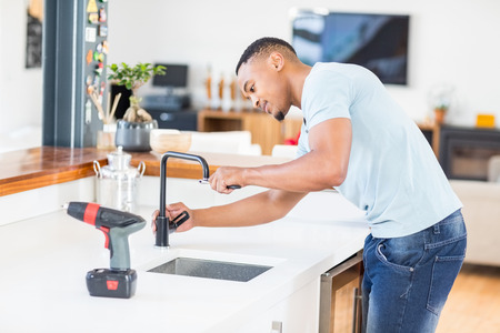 tightening: Close-up of man tightening tap with a wrench Stock Photo