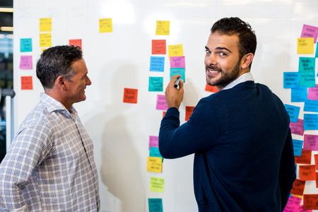 Jonge man glimlachend in de camera tijdens het schrijven op het bord, terwijl een collega staan naast hem