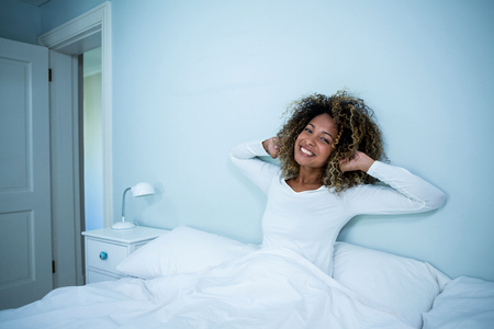 arms up: Woman waking up in bed at morning Stock Photo