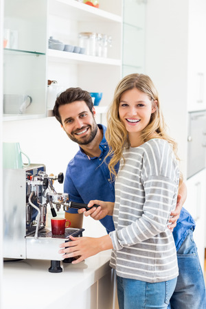 coffeemaker: Portrait of young couple preparing coffee from coffeemaker at home Stock Photo