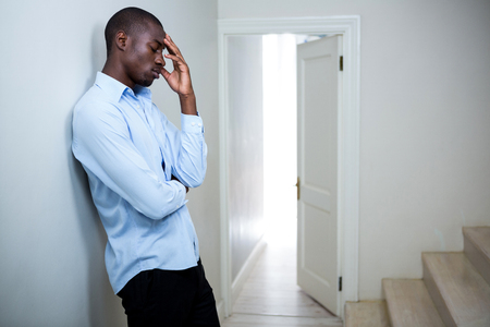 tensed: Tensed man leaning on wall at home