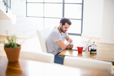 text messaging: Man text messaging on mobile at home Stock Photo
