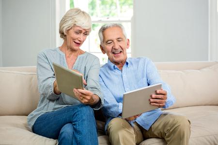 シニア カップル自宅のソファに座ってデジタル タブレットを使用して笑みを浮かべてください。