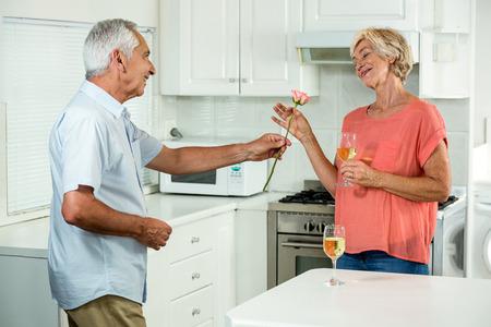 tomando refresco: Happy senior man giving rose to woman while standing in kitchen Foto de archivo