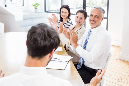 applauding: Workers are applauding and smiling thanks to someone on office