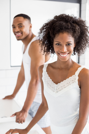 couple bathroom: Portrait of couple standing in bathroom and smiling at camera