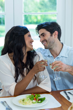 toasting wine: Couple toasting wine glasses while having meal at home Stock Photo
