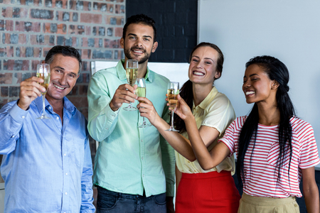 champagne flutes: Colleagues toasting champagne flutes in office