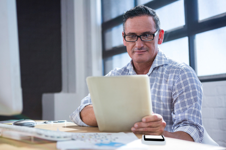 casual business man: Happy man using digital tablet in office