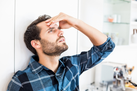 hand on forehead: Depressed man with hand on forehead at home